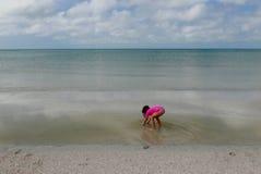 Meisje die over in ondiep water in kalm oceaanwater buigen stock afbeelding