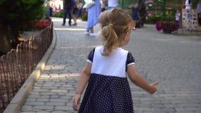 Meisje die in overvol park lopen stock footage