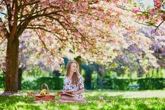 Meisje die picknick hebben en boek in kersentuin lezen royalty-vrije stock afbeelding