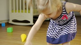 Meisje die plastic stuk speelgoed kubussen in een kinderen` s ruimte spelen stock video