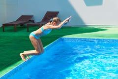 Meisje die in pool springen Stock Fotografie