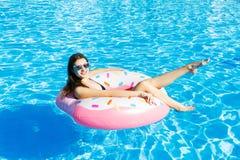 Meisje die pret hebben en op een opblaasbare roze ring lachen Vrouw in zwembad royalty-vrije stock afbeelding