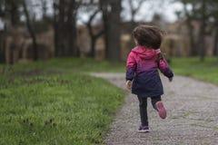 Meisje die pret hebben, die in park lopen stock fotografie