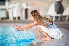 Meisje die pret met een plons dichtbij zwembad hebben Stock Foto