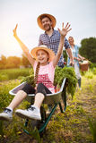 Meisje die pret met landbouwer in moestuin hebben Stock Foto's
