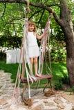 Meisje die pret op een schommeling hebben openlucht Kind het spelen, tuinspeelplaats Royalty-vrije Stock Afbeeldingen