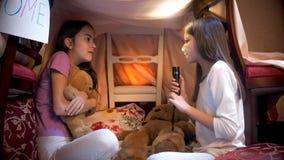 Meisje die in pyjama's met flitslicht eng verhaal vertellen aan haar vriend royalty-vrije stock foto