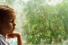 Meisje die regendruppels op het venster bekijken Stock Afbeeldingen