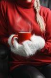 Meisje die in rode sweater en witte vuisthandschoenen kop houden Stock Afbeelding