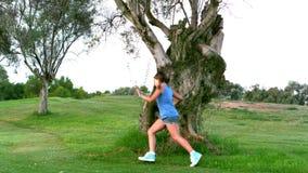 Meisje die rond een grote boom lopen stock footage
