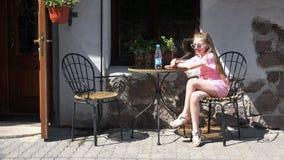 Meisje die rond met een fles water bij een koffietafel voor de gek houden stock videobeelden