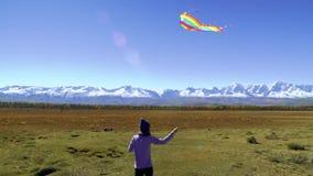 Meisje die rond met een vlieger op de bergen lopen Het concept van de vrijheid stock videobeelden