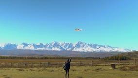 Meisje die rond met een vlieger op de bergen lopen Het concept van de vrijheid stock footage