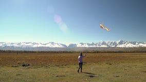 Meisje die rond met een vlieger op de bergen lopen Het concept van de vrijheid stock video