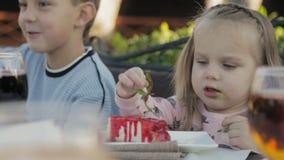 Meisje die saus van de kaastaart in de kinderen` s in openlucht koffie eten stock videobeelden
