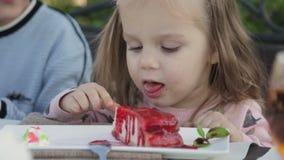 Meisje die saus van de kaastaart in de kinderen` s in openlucht koffie eten stock footage