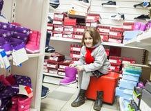 Meisje die schoenen in kinderen` s opslag proberen stock foto