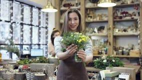Meisje die in schort een klein boeket van bloemen in een glaskruik het houden, toont het dan aan de camera stock footage