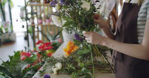Meisje die in schort samenstelling die van mooie kleurrijke bloemen maken bos houden stock videobeelden