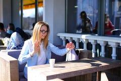 Meisje die selfie door smartphone maken en bij koffie met kop thee zitten royalty-vrije stock foto's