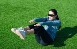 Meisje die situps op het gras, openluchttraining doen royalty-vrije stock foto's