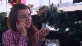 Meisje die in slim horloge door celtelefoon spreken in een restaurantlijst, glas bier op de lijst stock footage