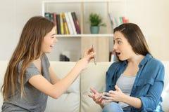Meisje die slimme telefooninhoud tonen aan een verbaasde vriend stock afbeeldingen
