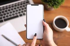 Meisje die smartphone gebruiken op het werk Het witte scherm royalty-vrije stock fotografie