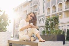 Meisje die smartphone gebruiken terwijl het rusten op houten bank stock fotografie