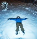 Meisje die in sneeuwnacht liggen Stock Fotografie