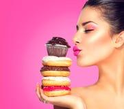 Meisje die snoepjes en kleurrijke donuts nemen Stock Foto's