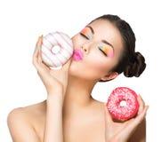Meisje die snoepjes en kleurrijke donuts nemen Stock Afbeeldingen