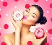 Meisje die snoepjes en kleurrijke donuts nemen Stock Afbeelding