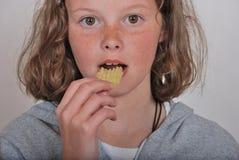 Meisje die spaander eten Stock Afbeelding