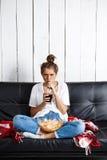 Meisje die spaanders eten, drinkend soda, het letten op TV, die bij bank zitten Stock Foto's