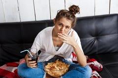 Meisje die spaanders eten, drinkend soda, het letten op TV, die bij bank zitten Stock Fotografie