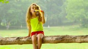 Is meisje die spelen met zeepbels in de zomertuin de het charmeren achtergrond vaag Langzame Motie stock video