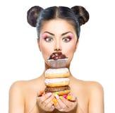 Meisje die stapel van kleurrijke donuts en muffin nemen Royalty-vrije Stock Afbeeldingen