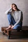 Meisje die in sweater haar hoofd houden Grijze achtergrond Royalty-vrije Stock Foto's
