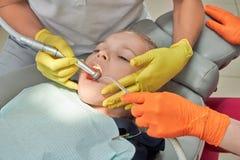 Meisje die tanden in tandheelkundekliniek behandelen stock foto's