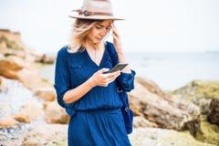Meisje die telefoon, de Zomerportret met behulp van van jonge vrouw in bruine hoed openlucht het hebben van pret op het overzees Stock Foto
