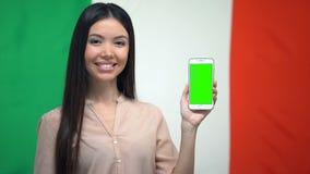 Meisje die telefoon met het groene scherm, Italiaanse vlag op achtergrond, vertaler tonen stock footage