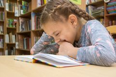 Meisje die terwijl het lezen van een boek in de bibliotheek lachen stock afbeeldingen