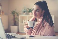 Meisje die thuis op de kop van de vloerholding van koffie zitten en royalty-vrije stock afbeeldingen