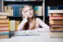 Meisje die of tijdens het voorbereiden van thuiswerk denken dromen stock fotografie