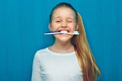 Meisje die toothy borstel met tanden houden stock foto