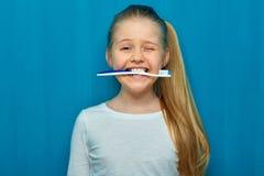 Meisje die toothy borstel met tanden houden stock foto's
