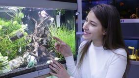 Meisje die tropische vissen in aquarium bekijken stock footage