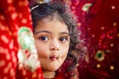 Meisje die tussen Saris gluren Royalty-vrije Stock Afbeelding