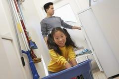 Meisje die Vader To Wash Clothes helpen Stock Foto